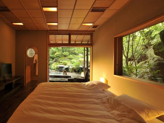 Room of the Gora Kadan ryokan in Hakone. It shows in the foreground a bed with white cushions and sheets. Behind the headboard, a window overlooks a verdant Japanese garden. At the back of the room a large door opens onto a private onsen.
