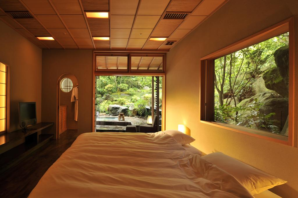 Chambre du ryokan Gora Kadan à Hakone. On y voit au premier plan un lit avec des coussins et des draps blancs. Derrière la tête de lit, une fenêtre donne sur un jardin japonais verdoyant. Au fond de la chambre une grande porte s'ouvre sur un onsen privé.