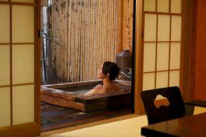 Um onsen privado no Rikyuan Ryokan de Hakone, Japão. Uma mulher toma seu banho quente atrás de portas corrediças de papel. O banho parece estar fora desde que há uma partição de bambu.