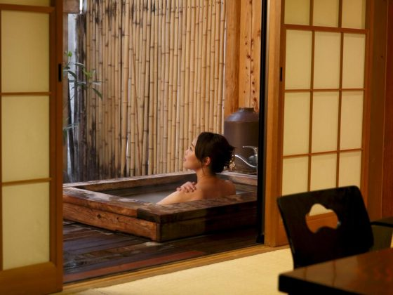 A private onsen in the Rikyuan Ryokan of Hakone, Japan. A woman takes her hot bath behind sliding paper doors. The bath seems to be outside since there is a bamboo partition.