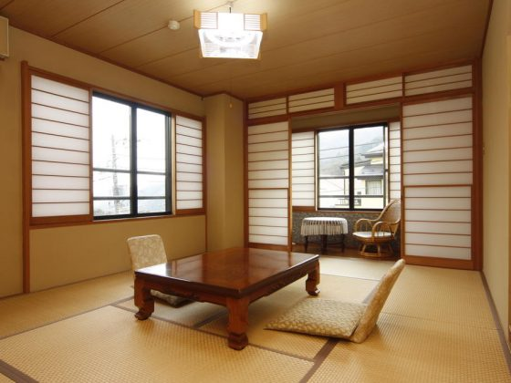 A room at the traditional hotel Umimoto in Hakone, Japan. The room is covered with tatami mats, the walls are yellow and there is a Japanese style sliding door. A wooden table and two cushions are in the middle of the room.
