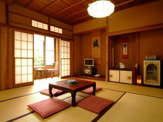 A traditional room in the Tsukinoya Hotel, Hakone. There is a tatami floor with red cushions and a red wooden table. The back wall respects the Japanese tradition, with a lantern, kakemonos, a fridge and a small TV.