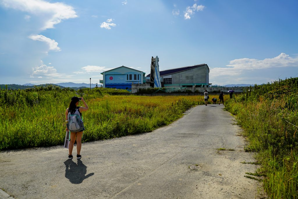 A group of tourists takes a picture of the Ukedo primary school. It is one of the only buildings left standing in Namie, Fukushima after the 2011 tsunami.