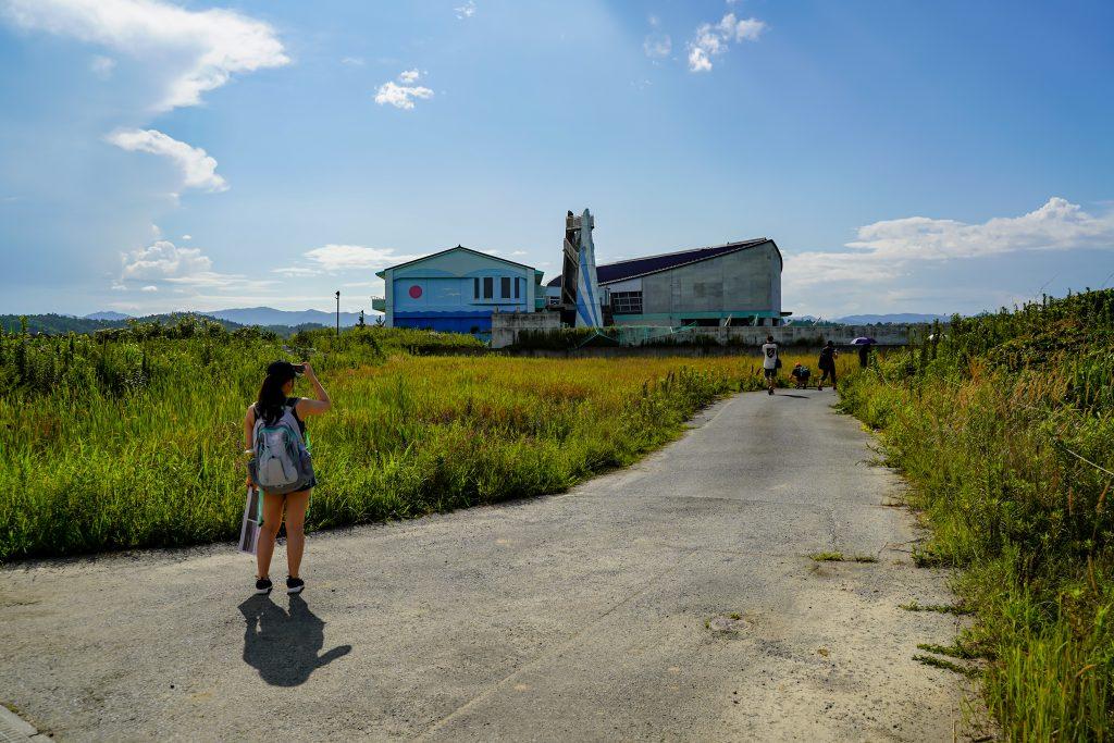 Un groupe de touriste prend en photo l'école primaire d'Ukedo. C'est l'un des seuls bâtiments à être resté debout à Namie, Fukushima après le tsunami de 2011.