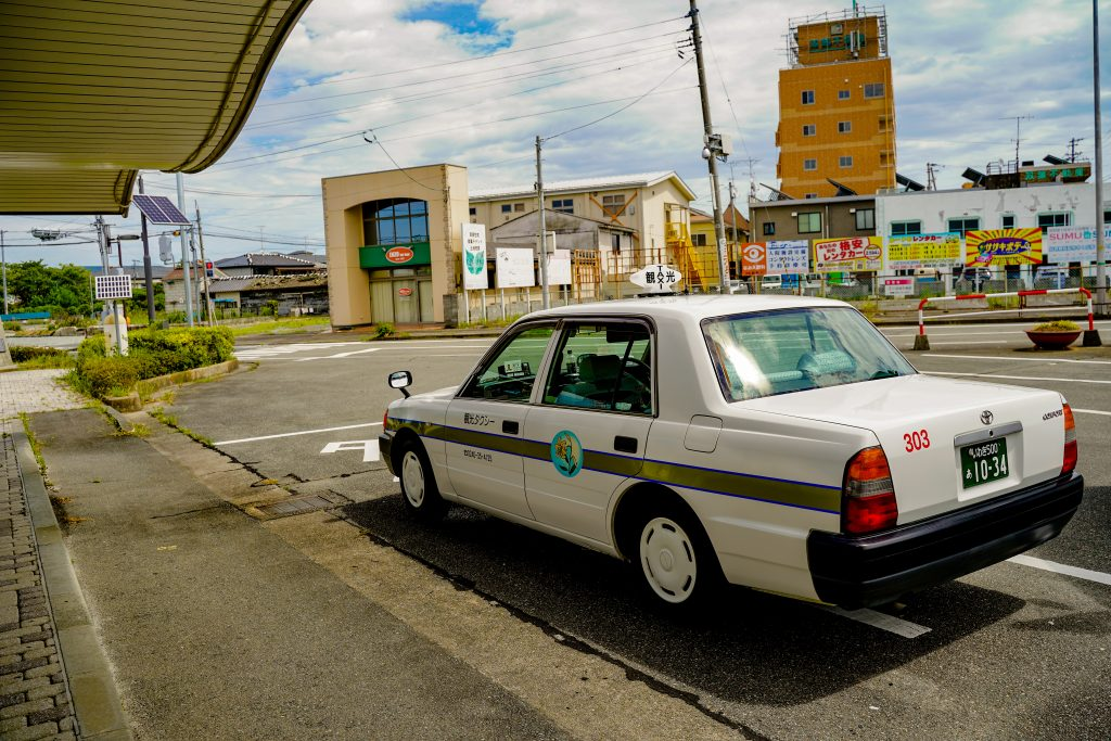 A white taxi parked in front of Namie Station in Fukushima Prefecture.