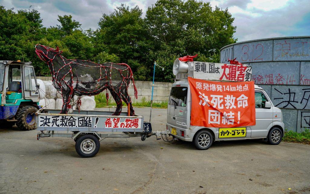 Un char composé d'un keicar et d'une remorque contenant une statue de vache. Plusieurs messages visant à alerter sur la situations des fermiers de Fukushima sont inscrits sur le véhicule.